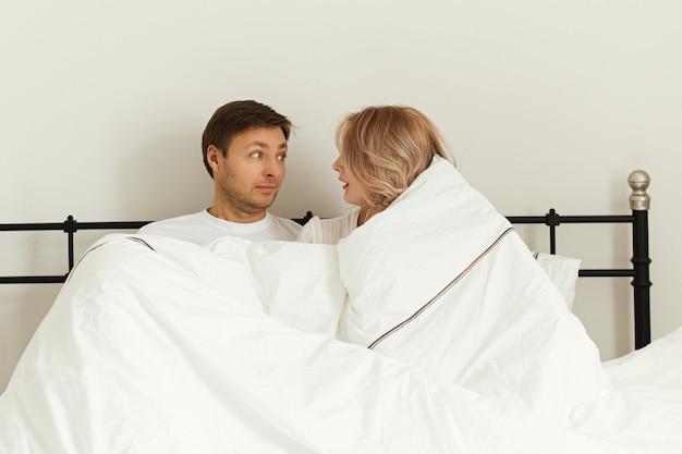 Echtpaar in bed. verbazing, word 's ochtends wakker