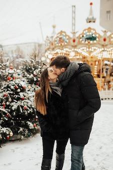 Echtpaar in de buurt van carrousel op kerstmarkt