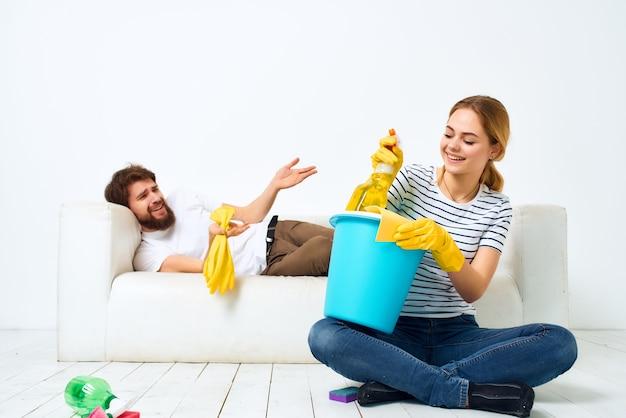 Echtpaar in de buurt van de bank schoonmaak van het appartement dienstverlening