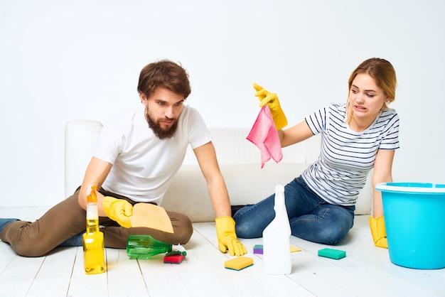 Echtpaar in de buurt van de bank schoonmaken van het appartement dienstverlening
