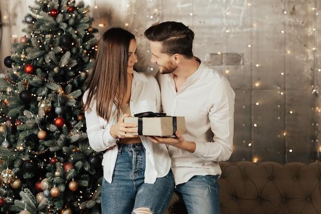 Echtpaar in de buurt van de kerstboom in de woonkamer. jong vrolijk paar verliefd op een kerstcadeau. man geeft cadeau aan zijn gelukkige vrouw.