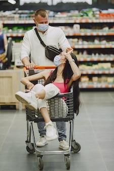 Echtpaar in een supermarkt. dame in een medisch masker. mensen maken parchases.