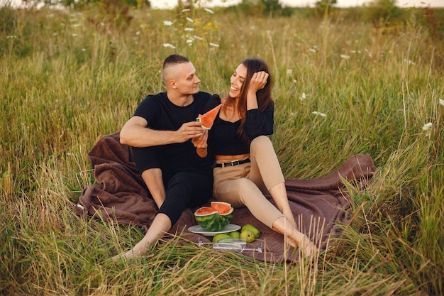 Echtpaar in een veld. vrouw in een zwarte blouse. mensen met watermeloen.