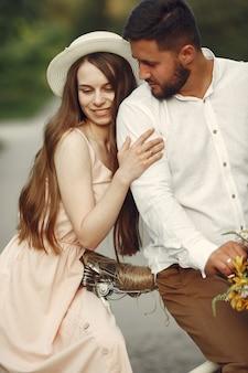 Echtpaar in een zomerpark. mensen met vintage fiets. meisje in een hoed.