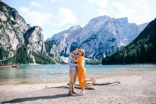 Echtpaar in elegante kleding omarmd aan de oever van het meer van braies. prachtige rotsachtige bergen