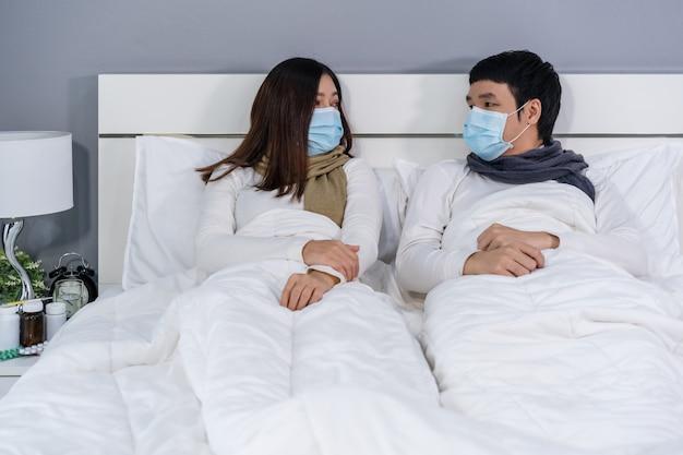 Echtpaar in medische maskers praten samen op bed, bescherming tegen pandemie concept coronavirus.