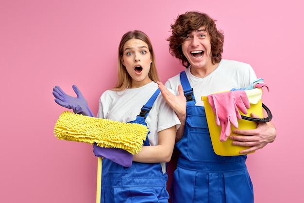 Echtpaar in overall en rubberen handschoenen kijken naar het schoonmaken van gereedschappen van de cameragreep die over roze studioachtergrond worden geïsoleerd