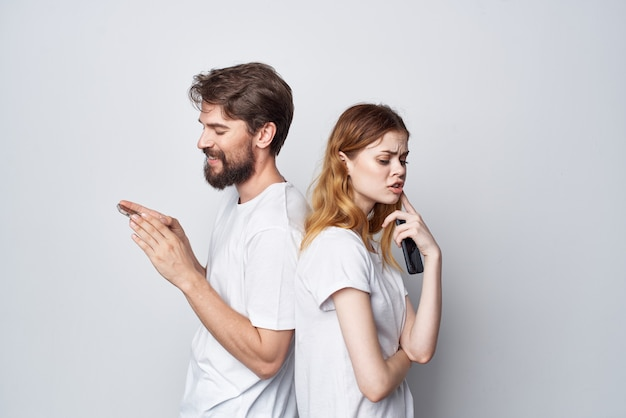 Echtpaar in witte t-shirts met telefoons in hun handen lichte achtergrond