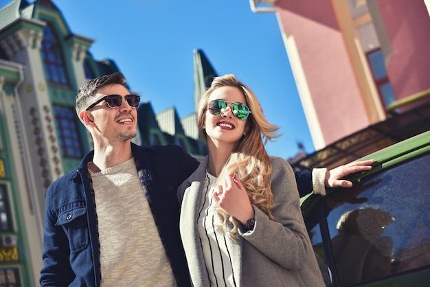 Echtpaar in zonnebril permanent in de buurt van de auto en op zoek naar nieuw appartement