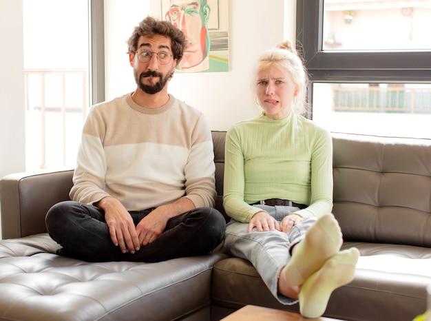 Echtpaar kijkt verbaasd en verward, bijt op lip met een nerveus gebaar, het antwoord op het probleem niet wetend