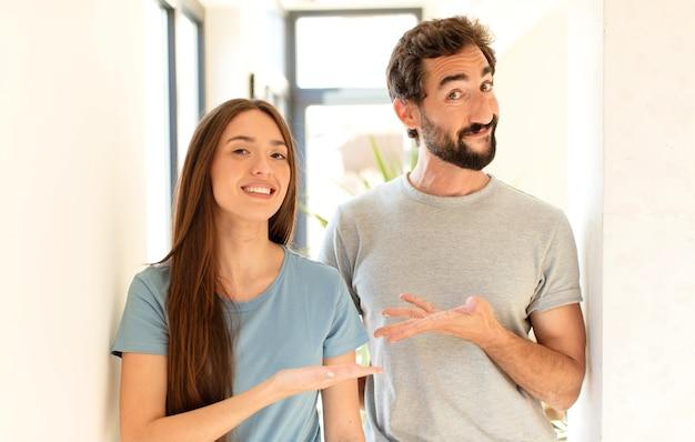 Echtpaar lacht vrolijk, voelt zich gelukkig en toont een concept in kopie ruimte met handpalm