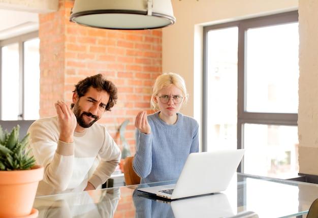 Echtpaar maakt een capice of geldgebaar en zegt dat u uw schulden moet betalen!
