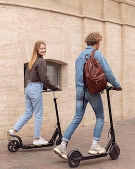 Echtpaar met behulp van elektrische scooters in de stad