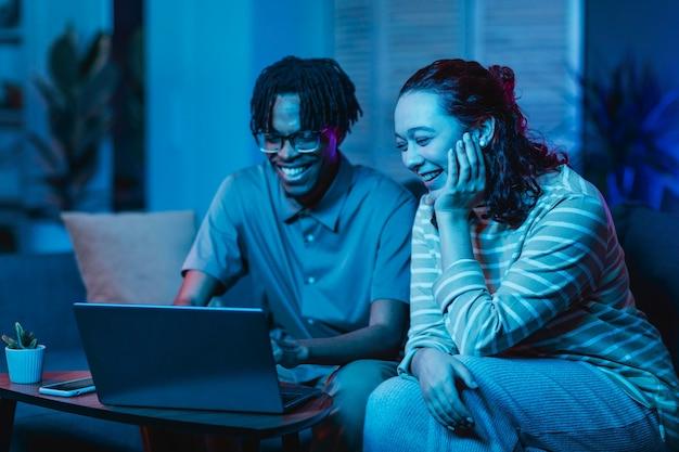 Echtpaar met behulp van laptop terwijl op de bank thuis samen