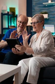 Echtpaar met behulp van video-oproep technologie zwaaien