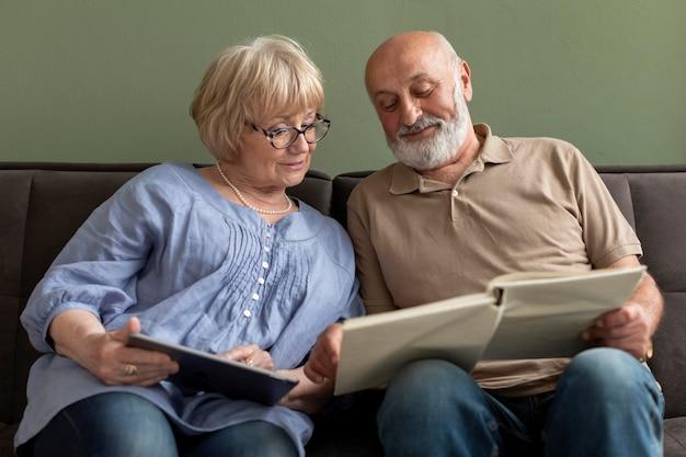Echtpaar met boek en tablet binnenshuis