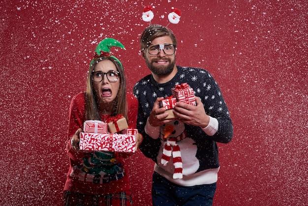 Echtpaar met cadeautjes staan in de sneeuw