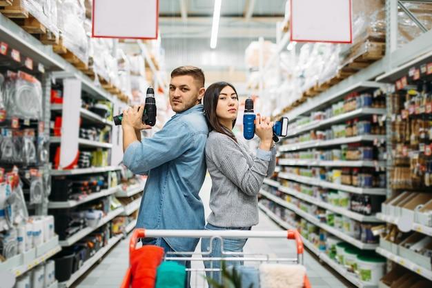 Echtpaar met elektrische schroevendraaiers, afdeling elektrisch gereedschap in de supermarkt