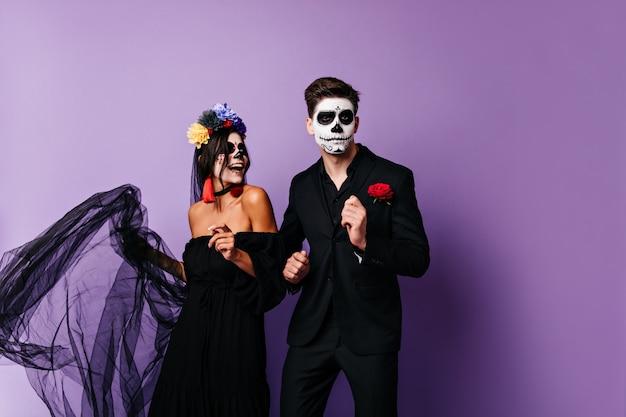 Echtpaar met geschilderde gezichten die rondhangen. foto van donkerharige meisje in beeld van bruid en haar vriendje in klassiek kostuum.