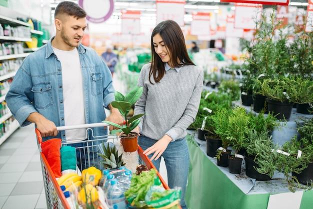Echtpaar met kar in afdeling planten en bloemen supermarkt, familie winkelen. klanten in de winkel, kopers in de markt