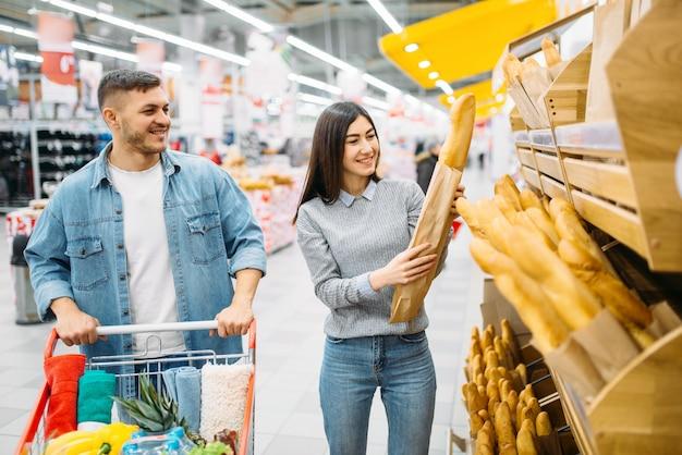Echtpaar met kar kiezen van vers brood in een supermarkt, familie winkelen. klanten in de winkel, kopers in de markt