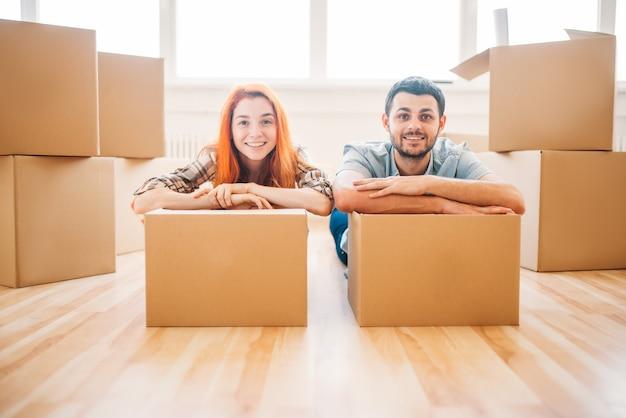 Echtpaar met kartonnen dozen in handen, nieuw huis