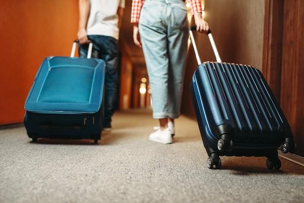 Echtpaar met koffer die door de gang van het hotel loopt