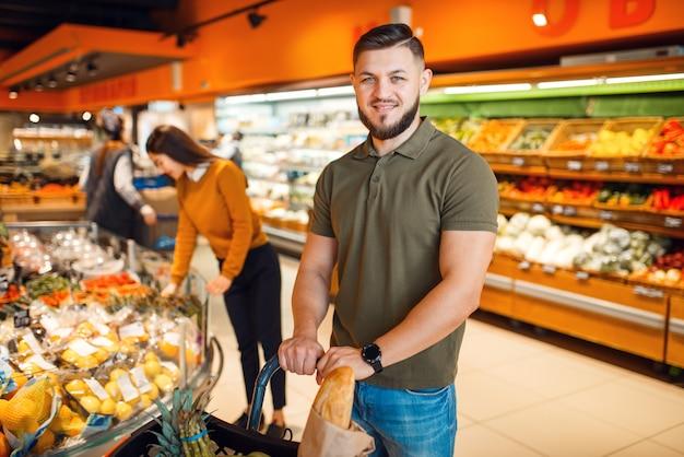 Echtpaar met mand in kruidenierswinkel-supermarkt samen