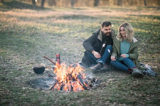 Echtpaar met marshmallows in de buurt van kampvuur