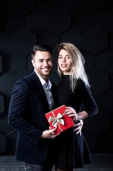 Echtpaar met rode geschenkdozen op een donkere achtergrond. modellen kijken naar camera. viering en romantisch concept.
