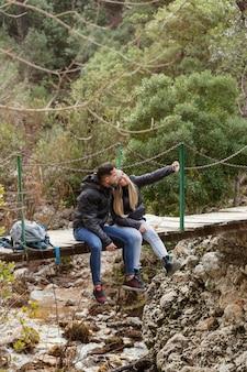 Echtpaar met rugzak zittend op de brug