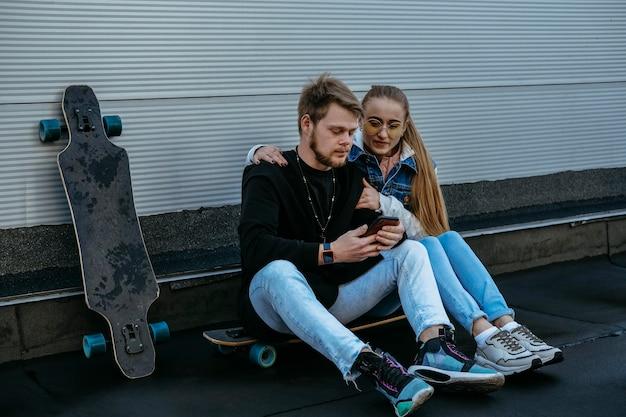 Echtpaar met skateboard en smartphone buitenshuis