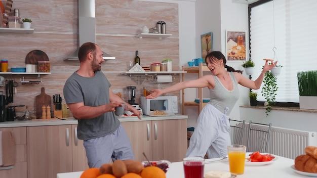 Echtpaar plezier dansen in de keuken tijdens het ontbijt. zorgeloze man en vrouw lachen, zingen, dansen luisteren mijmerend, gelukkig en zorgeloos leven. positieve mensen. Premium Foto