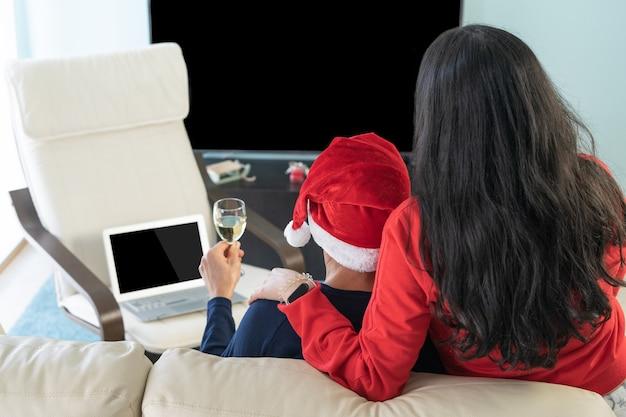 Echtpaar roosteren voor de laptop met kerstmis. viering in de verte.