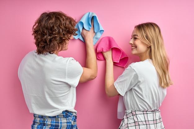 Echtpaar schoonmaken, huishoudelijk werk doen, samen huishoudelijke klusjes doen, met behulp van vodden. blanke man en vrouw poseren