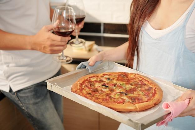 Echtpaar serveert pizza en wijn voor het diner