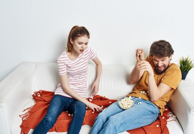 Echtpaar thuis op de bank rust popcorn fun