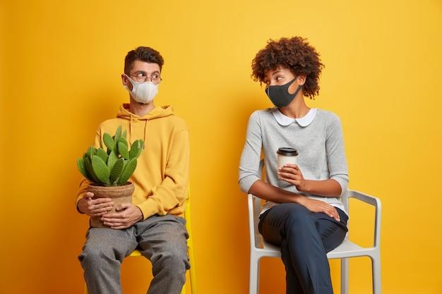Echtpaar van gemengd ras draagt beschermende gezichtsmaskers, houdt afstand, kijkt naar elkaar, voorkomt verspreiding van coronavirus op stoelen