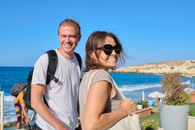 Echtpaar van middelbare leeftijd lopen hand in hand, man en vrouw die samen reizen