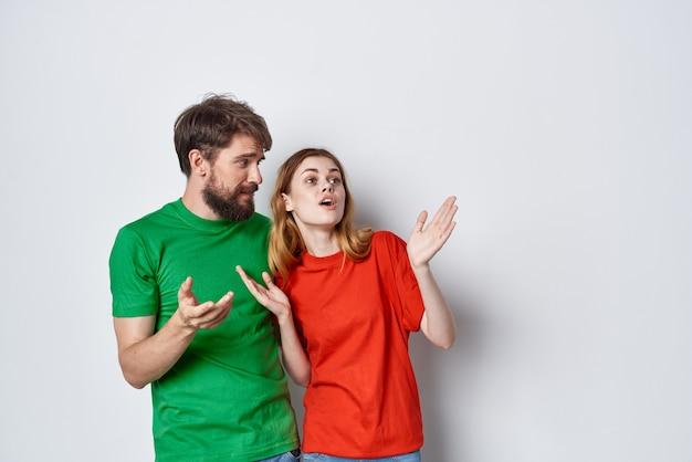 Echtpaar veelkleurige tshirts communicatie ruzie lichte achtergrond