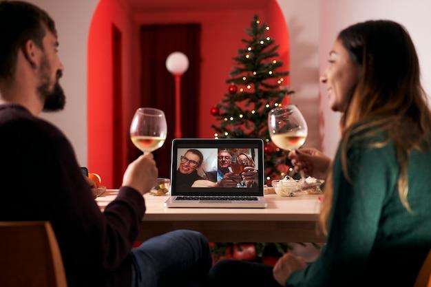 Echtpaar viert kerstmis in quarantaine vanwege covid 19 en voert een videogesprek met ouders en schoonfamilie. nieuw normaal in tijden van coronavirus.