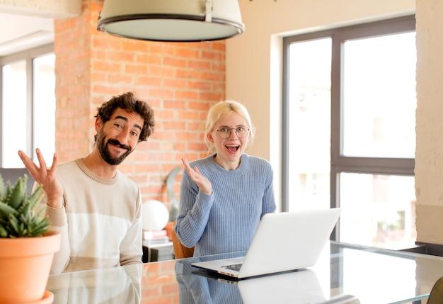 Echtpaar voelt zich gelukkig, verrast en opgewekt, lacht met een positieve instelling, realiseert zich een oplossing of idee