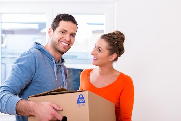 Echtpaar, vrouw en man, verhuizen met kisten