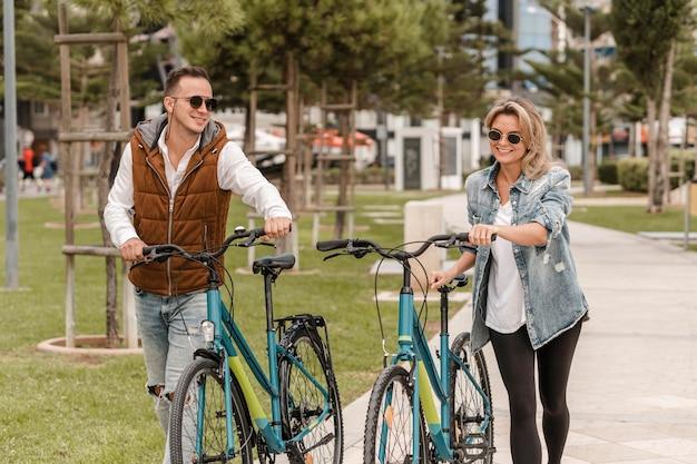 Echtpaar wandelen met een fiets naast hen buiten