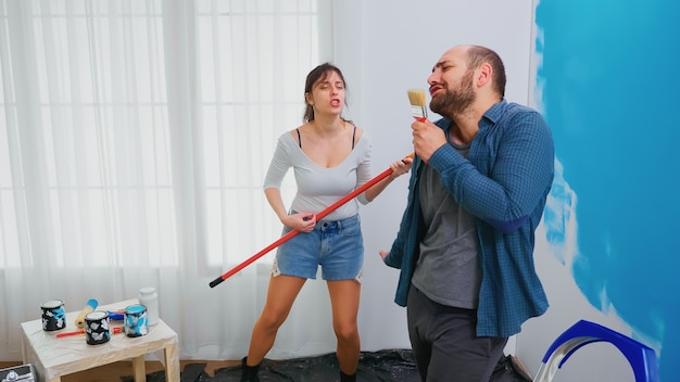 Echtpaar zingen op renovatie tools gedoopt in blauwe verf. vrolijk getrouwd stel tijdens home make-over. woondecoratie en renovatie in een gezellig appartement, reparatie en make-over