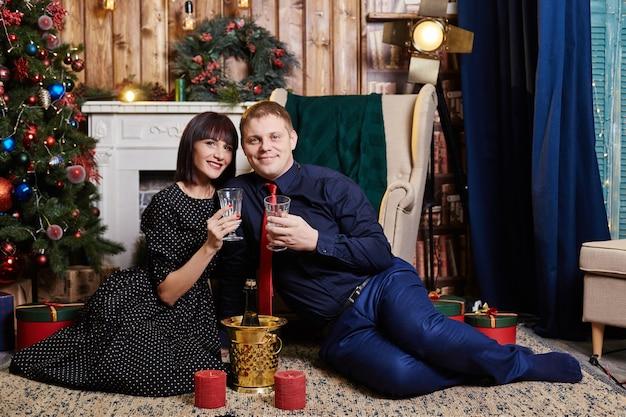 Echtpaar zit bij een kerstboom