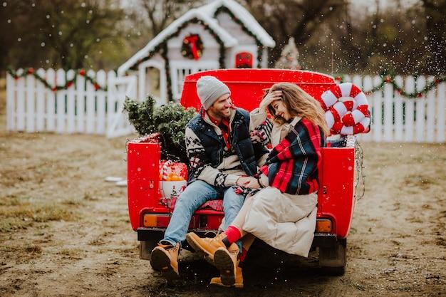 Echtpaar zit in de auto met kerstdecor sneeuwt