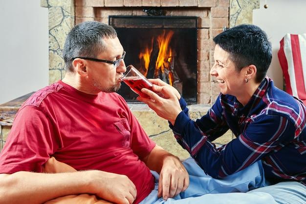 Echtpaar zit op zitzak stoelen en drinkt wijn bij de open haard tijdens het vieren van een evenement.