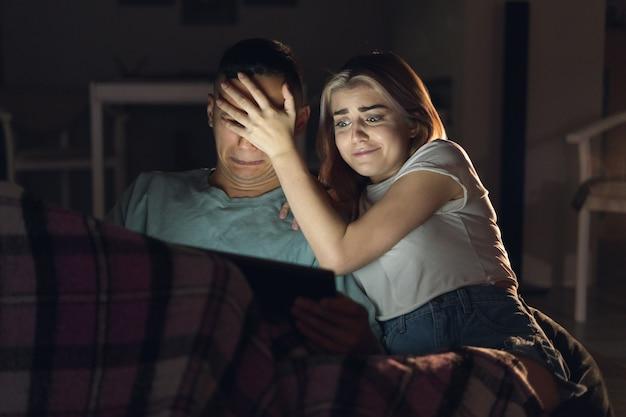 Echtpaar zitten in de avond thuis kijken naar een film