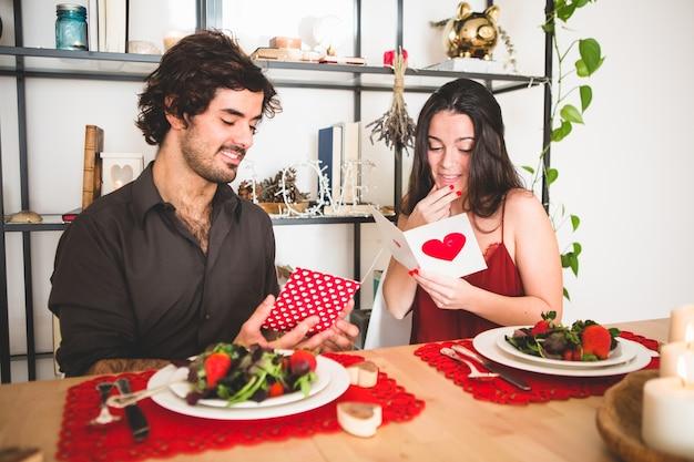 Echtpaar zittend aan een tafel te eten lezen romantische ansichtkaarten